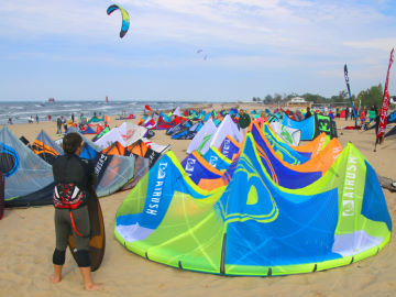 A beach packed full of kiteboarding gear