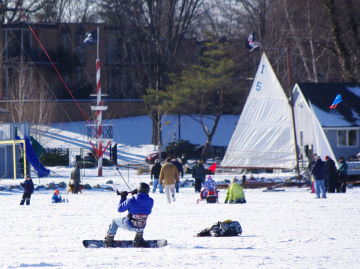 An ice boat and a snowkiter share the field at teh Reeds Lake Ice Fly